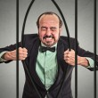 Businessman bending bars of his prison — Stock Photo #56600397