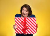 Happy excited woman opening red gift box — Stock Photo