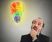 Man with thoughtful expression and light bulb over his head — Stock Photo