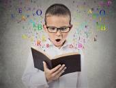 Child with glasses reading book — Stock Photo