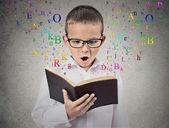 Child with glasses reading book — Foto de Stock