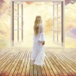 Beautiful girl in white dress standing looking into open window dreamland day light — Stock Photo #57127385