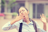 Sleepy young business woman covering with hand opened mouth yawning  — Stok fotoğraf