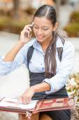 Businesswoman sitting outside reviewing financial statements paperwork talking on mobile phone — Stockfoto