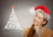 Woman in red santa helper hat looking at christmas tree  — Stock Photo
