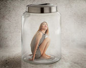 Young lonely woman sitting in glass jar — Stock Photo