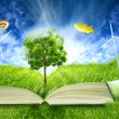 Green micro world, book covered with green grass wind energy turbines installed — Stock Photo #58395357