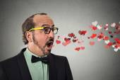Man sending kisses, red hearts coming flying out of open mouth — Stock Photo