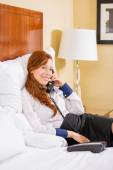 Smiling businesswoman talking on phone while sitting on the bed in hotel room. — Stock Photo