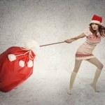 Santa helper girl pulling heavy christmas sack — Stock Photo #59834055
