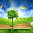 Green micro world, book covered with green grass wind energy turbines — Stock Photo #59834171