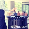 Woman's hand throwing empty paper coffee cup in recycling bin — Stock Photo #60467235