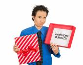 Confused skeptical man holding sign health care reform in gift box — ストック写真