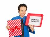 Man holding sign health care reform in gift box — Stock Photo