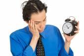 Sleeping young man holding alarm clock — Stock Photo