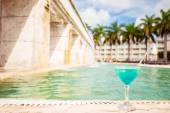 Glass of tropical cocktail on a background of swimming pool  — Stock Photo