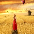 Woman in red dress standing walking through open wheat field — Stock Photo #62723851