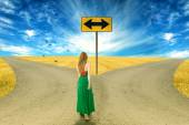 Young woman standing in front of two roads — Stockfoto