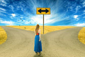 Young woman standing in front of two roads — Stock Photo