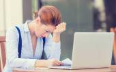 Stressed displeased worried business woman sitting in front of laptop computer  — Stock Photo