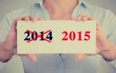 Businesswoman hands holding sign with year 2014 crossed and 2015 marked   — Stock Photo