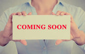 Businesswoman hands holding card sign with coming soon message  — Stock Photo