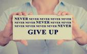 Businesswoman hands holding card with never give up sign message — Stock Photo