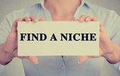Businesswoman hands holding card sign with Find a Niche message — Stock Photo