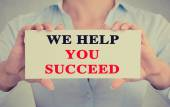 Businesswoman hands holding sign we help you succeed — Stock Photo