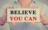 Closeup businesswoman hands holding sign with believe you can message — Stock Photo
