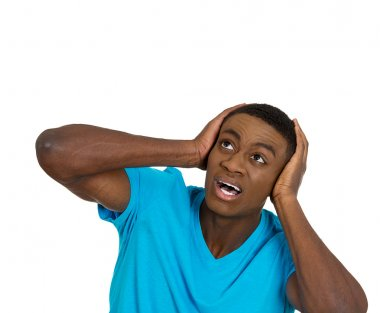 Unhappy stressed man covering his ears looking up