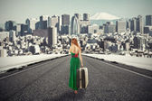 Woman with suitcase walking on road towards city talking on phone — Stock Photo