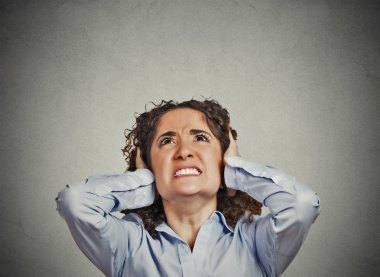 Angry woman covering ears looking up stop loud noise