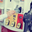 Woman hand swiping credit card at gas pump station — Stock Photo #64627137