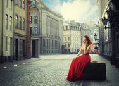 Woman sitting on suitcase talking on phone on quiet old town street  — Stock Photo