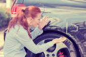 Frustrated woman checking pointing at car scratches dents — Stock Photo