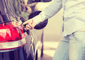 Woman opening car gas tank cap at petrol station  — Stock Photo