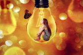 Lonely woman sitting inside light bulb looking at butterfly — Stock Photo