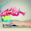 Hands on keyboard with colorful splashes out of monitor — Stock Photo #65721427