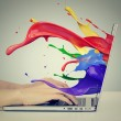 Hands on keyboard with colorful splashes out of monitor — Stock Photo #65721641