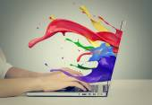 Hands on keyboard with colorful splashes out of monitor — Stock Photo