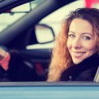 Happy winter woman, buckled up driving testing her new car — Stock Photo #66526081