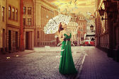 Woman with umbrella under a money rain — Stock Photo