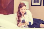 Young businesswoman relaxing on bed checking mobile phone — Stock Photo