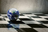 World earth on a chessboard isolated on grey wall background — Stock Photo