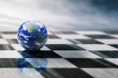 World on a chessboard isolated on blue sky background — Stock Photo
