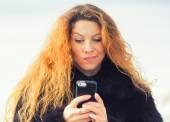 Upset sad skeptical unhappy woman texting on mobile phone — Stock Photo