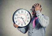 Stressed young man running out of time looking at wall clock  — Stock Photo