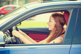 Happy beautiful young woman driving her new blue car — Stock Photo