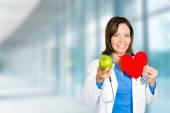 Female doctor healthcare professional with red heart green apple — Stock Photo